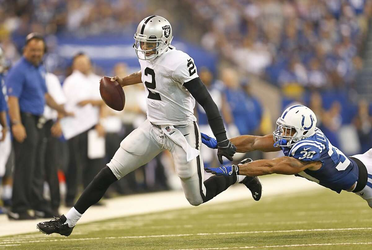 Oakland Raiders quarterback Terrelle Pryor (2) tries to get past Indianapolis Colts free safety LaRon Landry (30) in second half action on Sunday, September 8, 2013, in Indianapolis, Indiana. The Colts won the game 21-17. (Sam Riche/MCT)