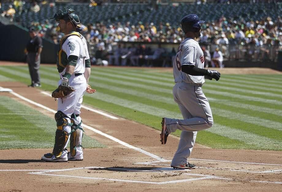 Jonathan Villar scores a run past Athletics catcher Stephen Vogt (21) on a double by Jose Altuve. Photo: Tony Avelar, Associated Press