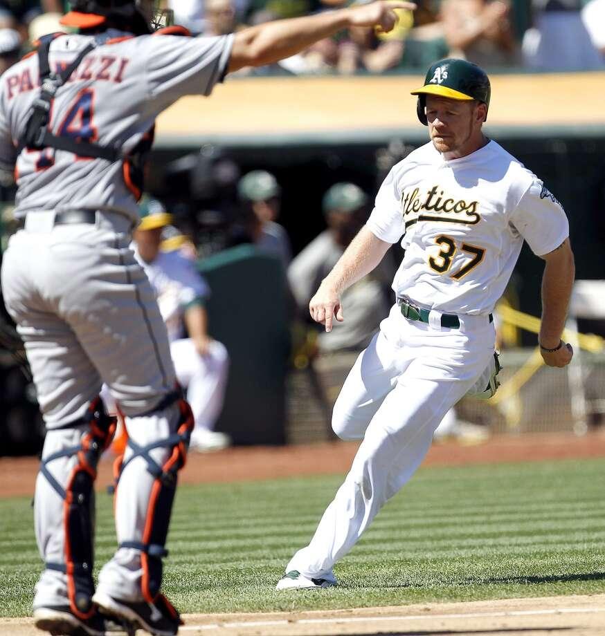 Brandon Moss (37) scores a run past Astros catcher Matt Pagnozzi (44) on a double by Yoenis Cespedes. Photo: Tony Avelar, Associated Press
