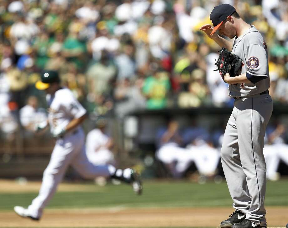 Astros starting pitcher Lucas Harrell stands on the mound as Seth Smith, background left, rounds the bases after hitting a three-run home run. Photo: Tony Avelar, Associated Press