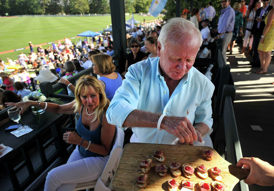 Rick Cason picks up some hors d'oeuvre for himself and Gail Heitz, left, during the second annual Royal Salute Jubilee Cup at the Greenwich Polo Club on Sunday, Sept. 8, 2013. Photo: Jason Rearick / Stamford Advocate