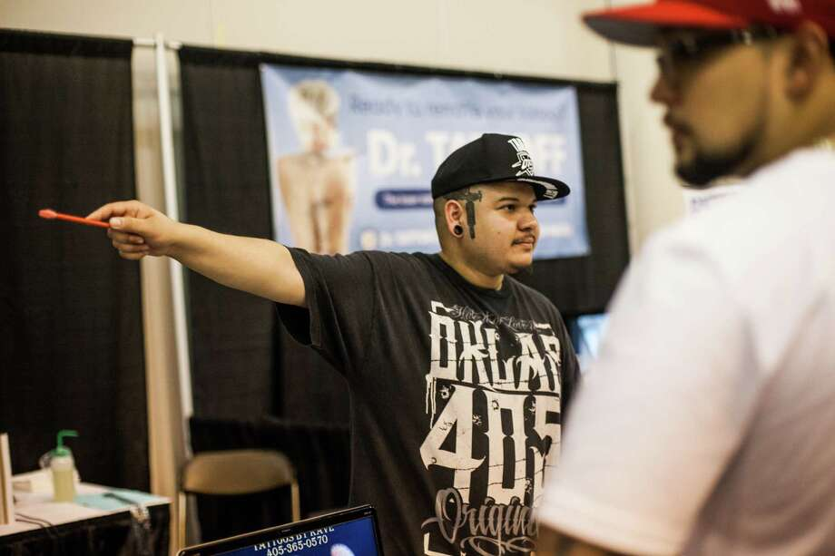Kave Gonzales from Oklahoma City, OK talks with a customer about tattoos during the Body Art Expo at the Reliant Center Saturday September 7, 2013. Photo: Michael Starghill, Jr. / © 2013 Michael Starghill, Jr.
