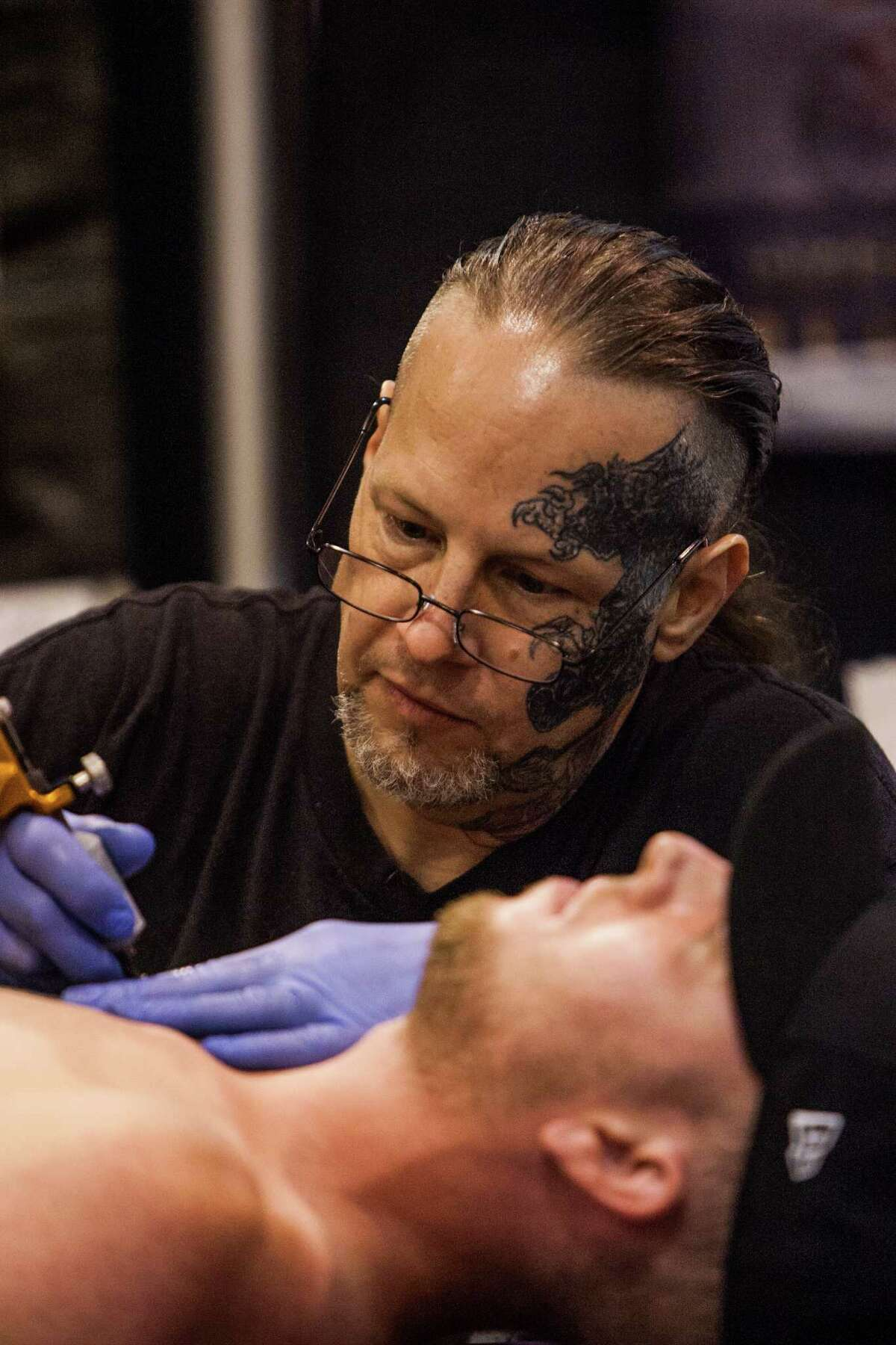 Edward Lee from Colorado Springs, CO tattoos a cutomer during the Body Art Expo at the Reliant Center Saturday September 7, 2013.