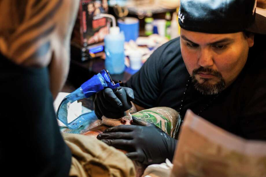 Rene Garcia of Big City Tattoos in Houston works on a customer's thigh during the Body Art Expo at the Reliant Center Saturday September 7, 2013. Photo: Michael Starghill, Jr. / © 2013 Michael Starghill, Jr.