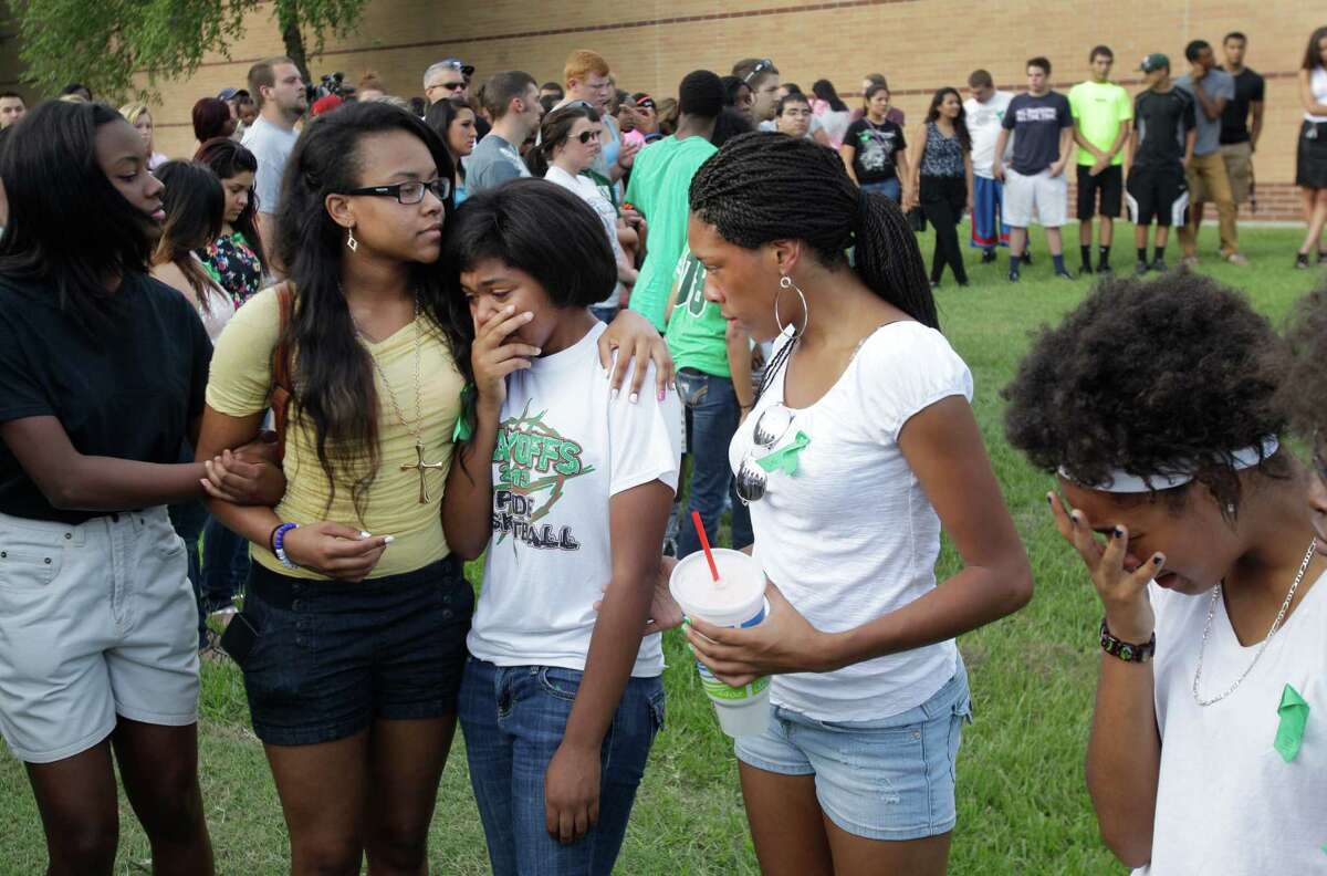 Spring High School students Justice Comeaux, left, a junior, Monique Sutton, a junior, Lavonne Williams, a junior, Chassidy Williams, a sophomore, and Bria Ferrier, right, a sophomore, comfort each other as they gather with more than 200 people to pray outside Spring High School Sunday, Sept. 8, 2013, in Spring. Students will return to classes on Monday to the school where Joshua Broussard, 17, a Spring High School student was fatally stabbed and three others injured at the school Wednesday, Sept. 3, 2013. Luis Alonzo Alfaro, 17, has been charged with murder.