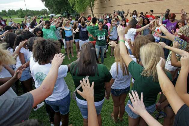 More than 200 people pray together outside Spring High School Sunday, Sept. 8, 2013, in Spring. Students will return to classes on Monday to the school where Joshua Broussard, 17, a Spring High School student was fatally stabbed and three others injured at the school Wednesday, Sept. 3, 2013.  Luis Alonzo Alfaro, 17, has been charged with murder. Photo: Melissa Philli