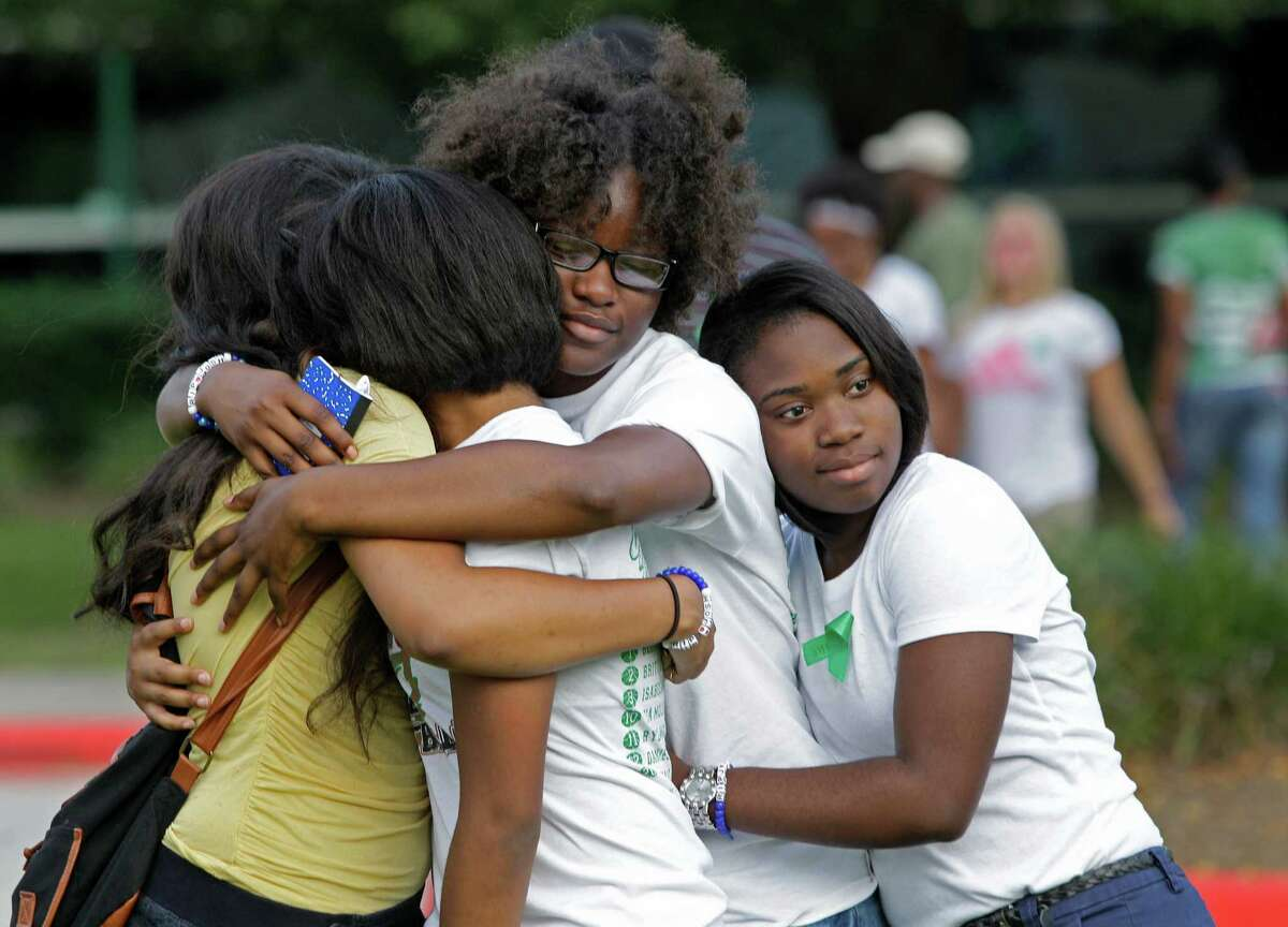A group of girls hug each other after attending a prayer session with more than 200 people outside Spring High School Sunday, Sept. 8, 2013, in Spring. Students will return to classes on Monday to the school where Joshua Broussard, 17, a Spring High School student was fatally stabbed and three others injured at the school Wednesday, Sept. 3, 2013. Luis Alonzo Alfaro, 17, has been charged with murder.
