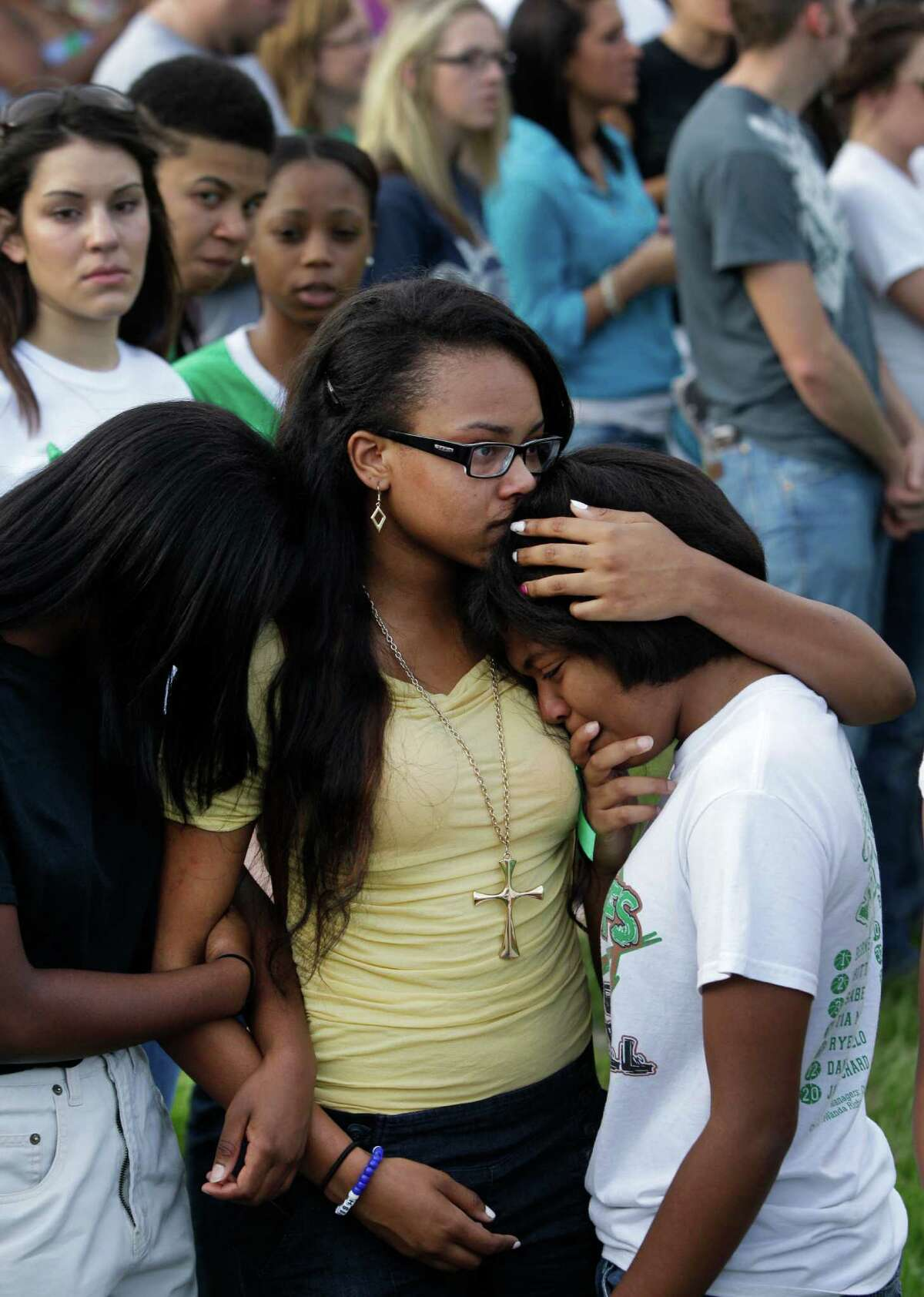 Justice Comeaux, left, a junior, Monique Sutton, center, a junior, Lavonne Williams, right, a junior, hug during gathering with more than 200 people to pray outside Spring High School Sunday, Sept. 8, 2013, in Spring. Students will return to classes on Monday to the school where Joshua Broussard, 17, a Spring High School student was fatally stabbed and three others injured at the school Wednesday, Sept. 3, 2013. Luis Alonzo Alfaro, 17, has been charged with murder.