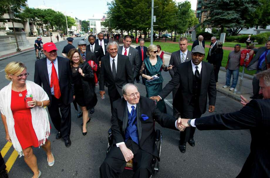 Friends, family and former players take the traditional trip down Court Street with former UH basketball coach Guy V. Lewis, center, before his induction into the Naismith Memorial Basketball Hall of Fame in Springfield, Mass. Photo: Johnny Hanson, Staff / © 2013  Houston Chronicle