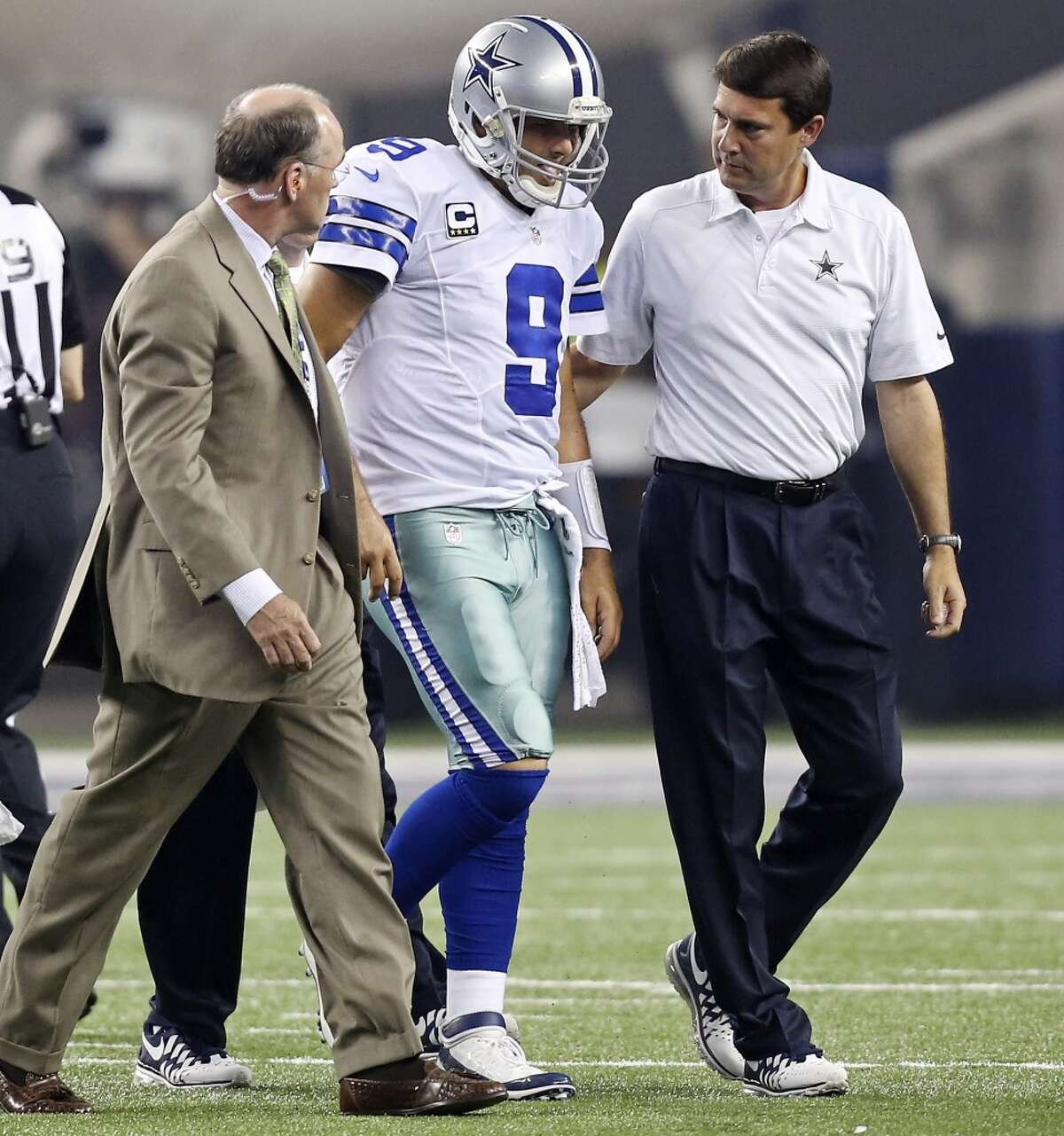 Dallas Cowboys' Tony Romo (center) walk off the field after being injured on a play during first half action against the New York Giants Sunday Sept. 8, 2013 at AT&T Stadium in Arlington, Tx.