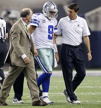 Dallas Cowboys' Tony Romo (center) walk off the field after being injured on a play during first half action against the New York Giants Sunday Sept. 8, 2013 at AT&T Stadium in Arlington, Tx. Photo: San Antonio Express-News