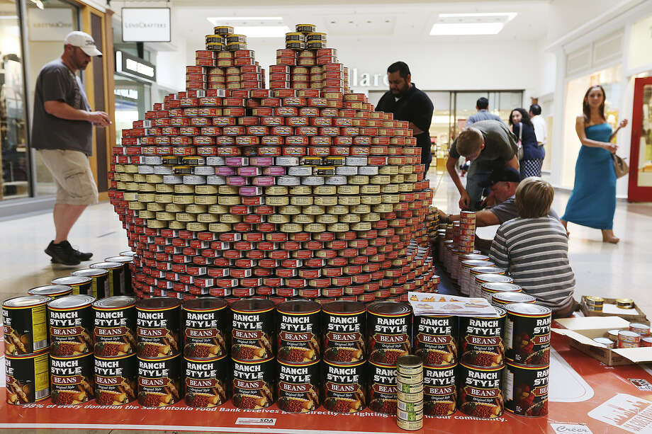The Mdn Architects team works on its Garfield-inspired entry in the eighth annual Canstruction. The 13 teams spent the day at North Star Mall constructing their entries with cans of food that will be donated to the San Antonio Food Bank. Photo: Jerry Lara, San Antonio Express-News