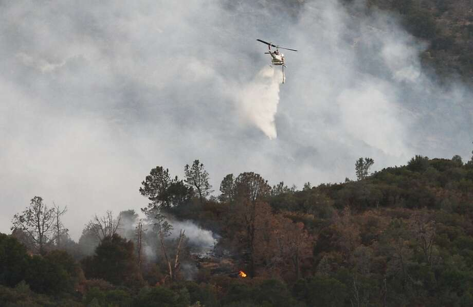 As some 250 firefighters struggle to contain the blaze, a Cal Fire helicopter drops water on the wildfire that had consumed more than 800 acres by Sunday night in the Mount Diablo State Park area. Steep terrain and dense vegetation made the battle more challenging. Photo: Raphael Kluzniok, The Chronicle