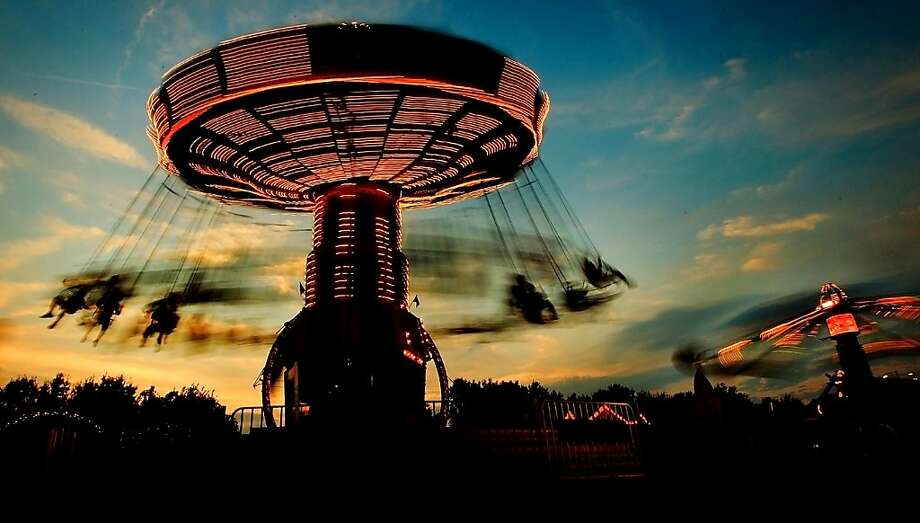 May the centrifugal force be with you: Fair-goers ride the Swinger on the last evening at the Delta Fair in Memphis, 
