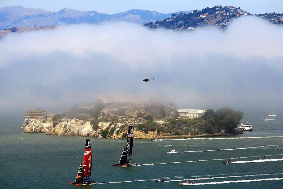 Eat my dust, Oracle: Emirates Team New Zealand speeds ahead of Oracle Team USA in front of a fog-shrouded 