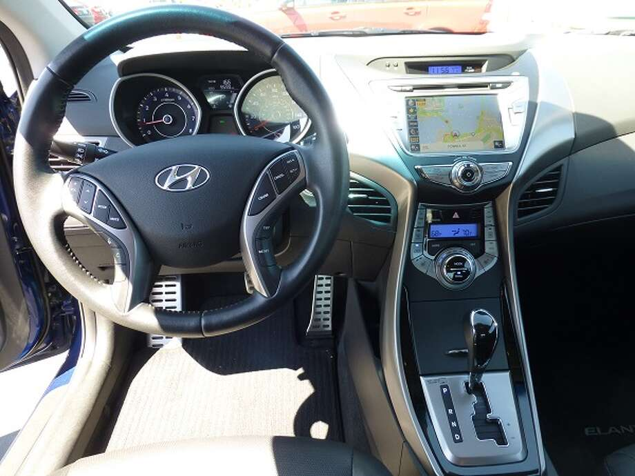It has a straightforward instrument panel, a center stack with the usual useful stuff – in this case, our Elantra Coupe SE had the optional $2,350 technology package that includes navigation, rear view camera and 360-watt stereo system. Oddly, there's a silvery slash of plastic to the left side of the navigation screen that does its best to reflect itself in the windshield, adding an annoying glare when the sun is at the right place, which was most of the time we were in the car