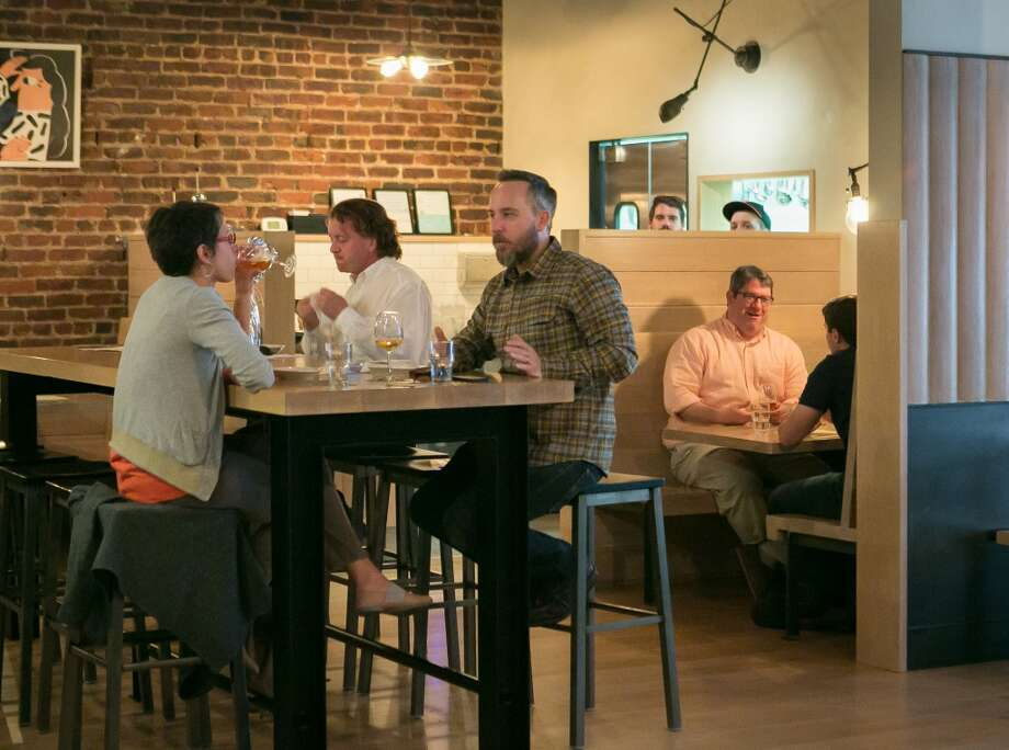 Diners enjoy dinner and a beer  at Mikkeller. Photo: John Storey, Special To The Chronicle