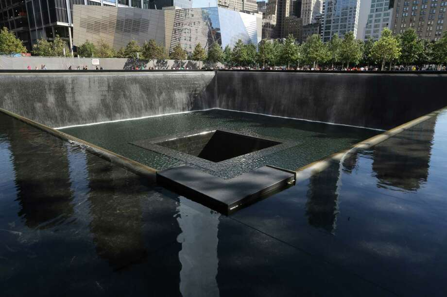 The National September 11 Museum is seen beyond the North Pool in the Memorial, Friday, Sept. 6, 2013 in New York. Construction is racing ahead inside the museum as the 12th anniversary of the Sept. 11, 2001 attacks draws near. Several more large artifacts have been installed in the cavernous space below the World Trade Center memorial plaza. (AP Photo/Mary Altaffer) ORG XMIT: NYMA114 Photo: Mary Altaffer, AP / AP