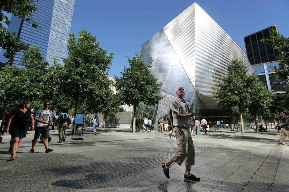 A visitor to the National September 11 Memorial and Museum takes in the sight as he walks past the museum, Friday, Sept. 6, 2013 in New York. Construction is racing ahead inside the museum as the 12th anniversary of the Sept. 11, 2001 attacks draws near. Several more large artifacts have been installed in the cavernous space below the World Trade Center memorial plaza. (AP Photo/Mary Altaffer) ORG XMIT: NYMA101 Photo: Mary Altaffer, AP / AP