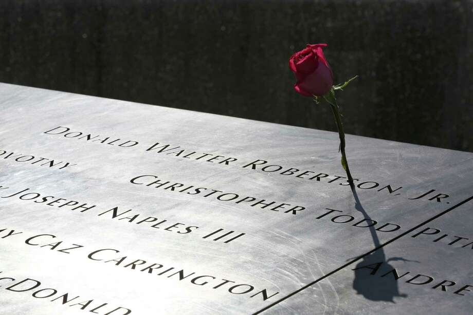 A rose is placed next to the name of a victim of the terrorist attacks on the World Trade Center at the North Pool of the National September 11 Memorial and Museum, Friday, Sept. 6, 2013, in New York. Construction is racing ahead inside the museum as the 12th anniversary of the Sept. 11, 2001 attacks draws near. Several more large artifacts have been installed in the cavernous space below the World Trade Center memorial plaza. (AP Photo/Mary Altaffer) ORG XMIT: NYMA115 Photo: Mary Altaffer, AP / AP
