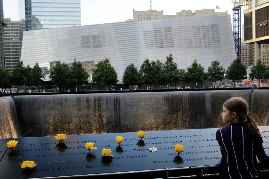 Charlotte Newman, 8, visits the National September 11 Memorial and Museum, Sunday, Sept. 8, 2013 in New York. Twelve years after terrorists destroyed the old World Trade Center, the new World Trade Center is becoming a reality, with a museum commemorating the attacks and two office towers where thousands of people will work set to open within the next year. (AP Photo/Mark Lennihan) ORG XMIT: NYR312 Photo: Mark Lennihan, AP / AP