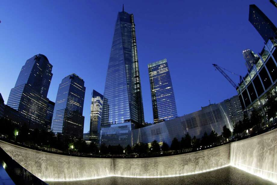 In this image made with a fisheye lens, One World Trade Center, center, rises above waterfalls at the National September 11 Memorial and Museum, Sunday, Sept. 8, 2013, in New York. Twelve years after terrorists destroyed the old World Trade Center, the new World Trade Center is becoming a reality, with a museum commemorating the attacks and two office towers where thousands of people will work set to open within the next year. (AP Photo/Mark Lennihan) ORG XMIT: NYR309 Photo: Mark Lennihan, AP / AP
