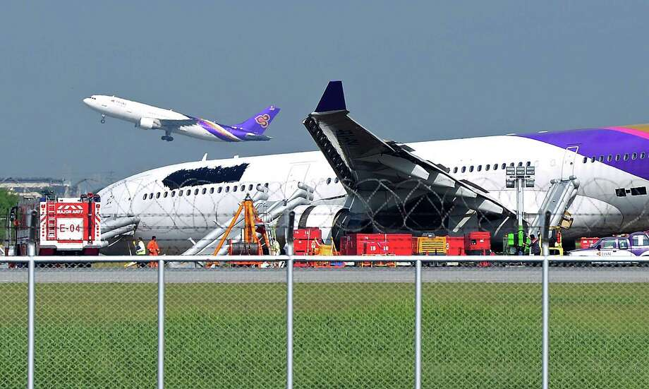 A Thai Airways plane (L) takes off as another (R), with its logo and name covered up, rests on ground the morning after it skidded off the runway at Suvarnabhumi International Airport in Bangkok on Monday. The incident late on Sunday, which injured more than a dozen passengers, involved an Airbus 330-300 carrying 287 passengers and 14 crew members on a flight from Guangzhou, the carrier said. (PORNCHAI KITTIWONGSAKUL/AFP/Getty Images) Photo: PORNCHAI KITTIWONGSAKUL, Ap/getty / 2013 AFP