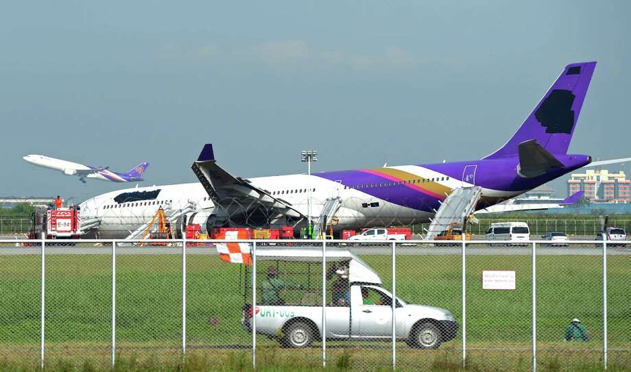 A Thai Airways plane, with its logo and name covered up, rests on ground the morning after it skidded off the runway at Suvarnabhumi International Airport in Bangkok on Monday. The incident late on Sunday, which injured more than a dozen passengers, involved an Airbus 330-300 carrying 287 passengers and 14 crew members on a flight from Guangzhou, the carrier said. (PORNCHAI KITTIWONGSAKUL/AFP/Getty Images) Photo: PORNCHAI KITTIWONGSAKUL, Ap/getty / 2013 AFP