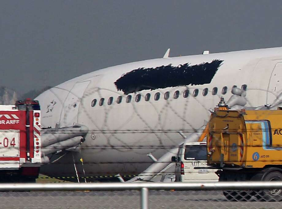 A damaged head section of a Thai Airways Airbus A330-300 is seen with the Thai Airways logo above windows blacked out at Suvarnabhumi International Airport in Bangkok, Thailand Monday. The plane carrying more than 280 people skidded off the runway while landing Sunday, injuring 14 passengers. After the accident, workers on a crane blacked out the logo on the tail and body of the aircraft. (AP Photo/Apichart Weerawong) Photo: Ap/getty