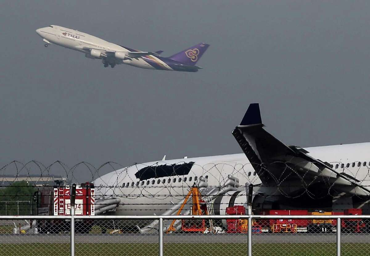 A Thai Airways passenger plane takes off over a damaged Thai Airways Airbus A330-300 at Suvarnabhumi International Airport in Bangkok, Thailand Monday, Sept. 9, 2013. The plane carrying more than 280 people skidded off the runway while landing at the airport Sunday, injuring 14 passengers. After the accident, workers on a crane blacked out the Thai Airways logo on the tail and body of the aircraft. (AP Photo/Apichart Weerawong)