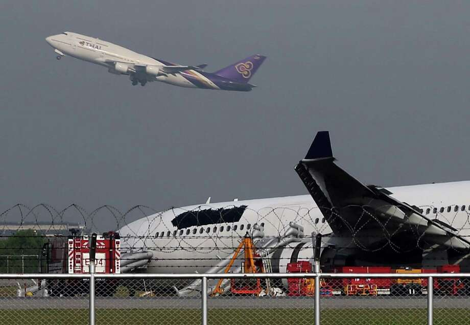 A Thai Airways passenger plane takes off over a damaged Thai Airways Airbus A330-300 at Suvarnabhumi International Airport in Bangkok, Thailand Monday, Sept. 9, 2013. The plane carrying more than 280 people skidded off the runway while landing at the airport Sunday, injuring 14 passengers. After the accident, workers on a crane blacked out the Thai Airways logo on the tail and body of the aircraft. (AP Photo/Apichart Weerawong) Photo: Ap/getty