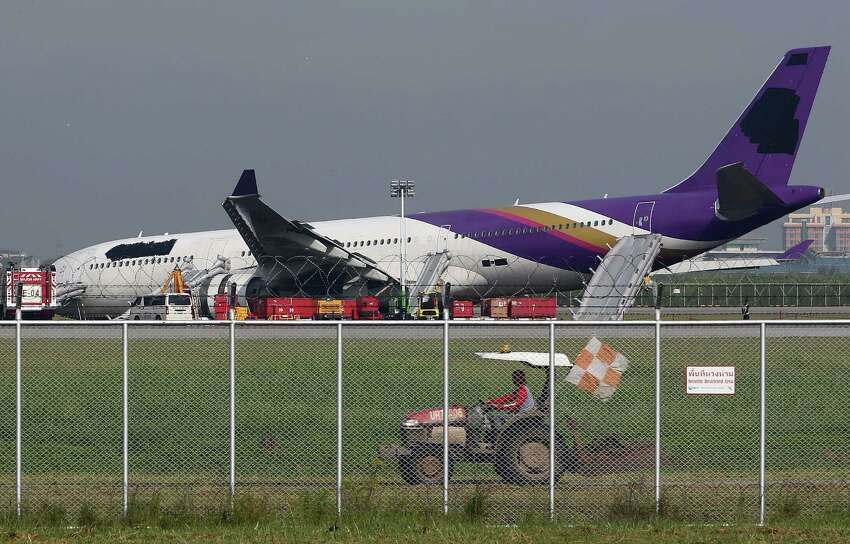 An airport worker drives a cart past a damaged Thai Airways Airbus A330-300 at Suvarnabhumi International Airport in Bangkok, Thailand Monday. The plane carrying more than 280 people skidded off the runway while landing Sunday, injuring 14 passengers. After the accident, workers on a crane blacked out the Thai Airways logo on the tail and body of the aircraft. (AP Photo/Apichart Weerawong)