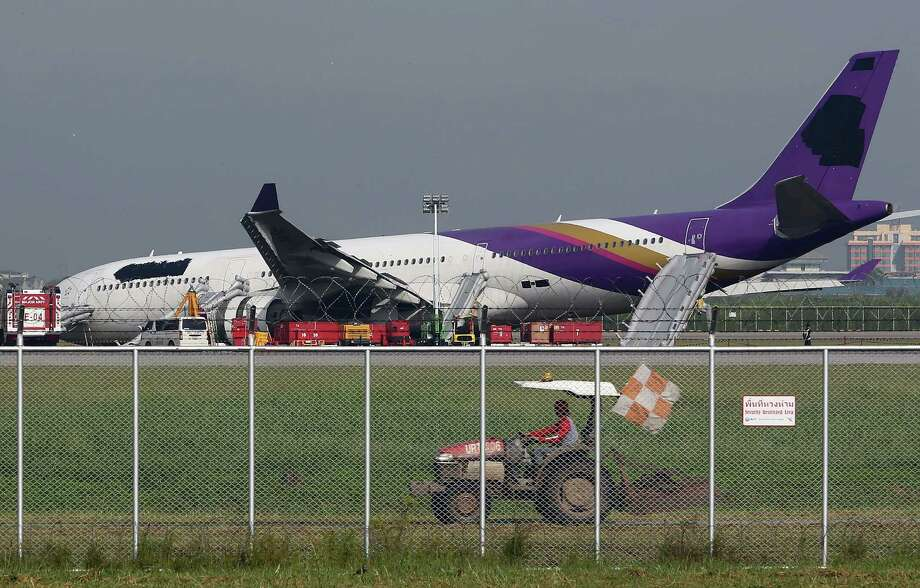An airport worker drives a cart past a damaged Thai Airways Airbus A330-300 at Suvarnabhumi International Airport in Bangkok, Thailand Monday. The plane carrying more than 280 people skidded off the runway while landing Sunday, injuring 14 passengers. After the accident, workers on a crane blacked out the Thai Airways logo on the tail and body of the aircraft. (AP Photo/Apichart Weerawong) Photo: Ap/getty