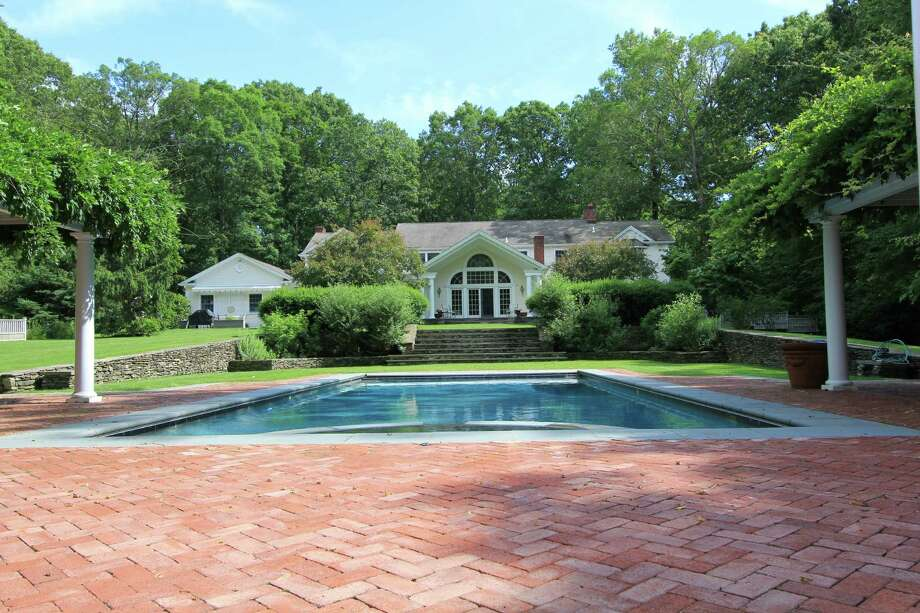 The 13-room Romanesque Colonial at 334 Lost District Drive in New Canaan boasts a backyard in-ground pool with separate pool house and spa. It is on the market for $2,495,000. Photo: Contributed
