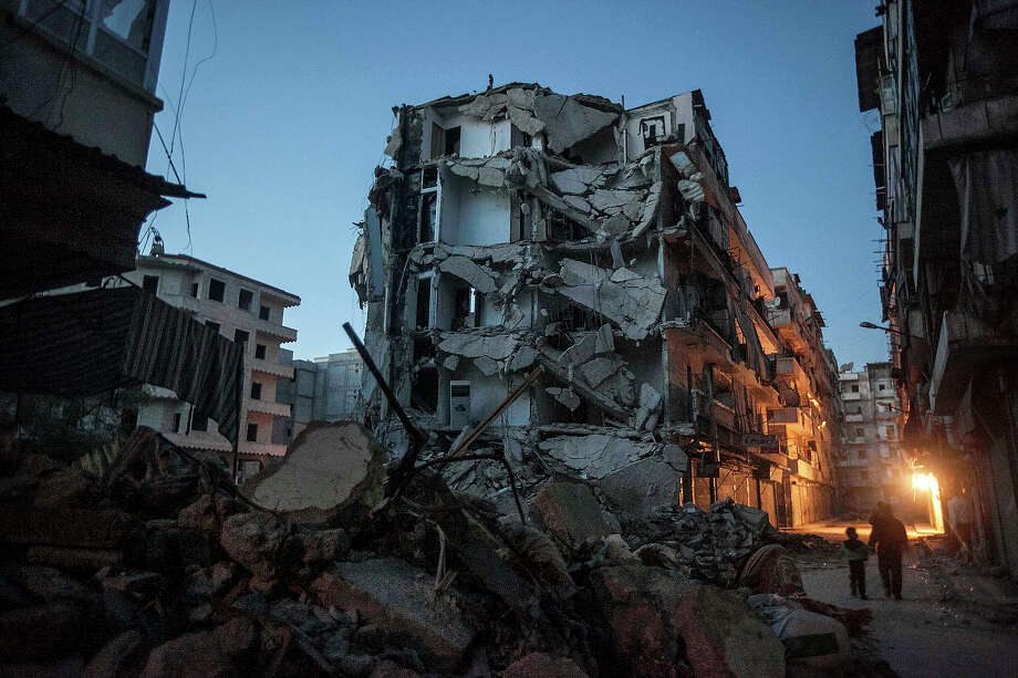 In this Sunday, Dec. 2, 2012 photo, residents walk past damaged buildings due to heavy fighting between Free Syrian Army fighters and government forces in Aleppo, Syria. Photo: Narciso Contreras, ASSOCIATED PRESS / AP2012
