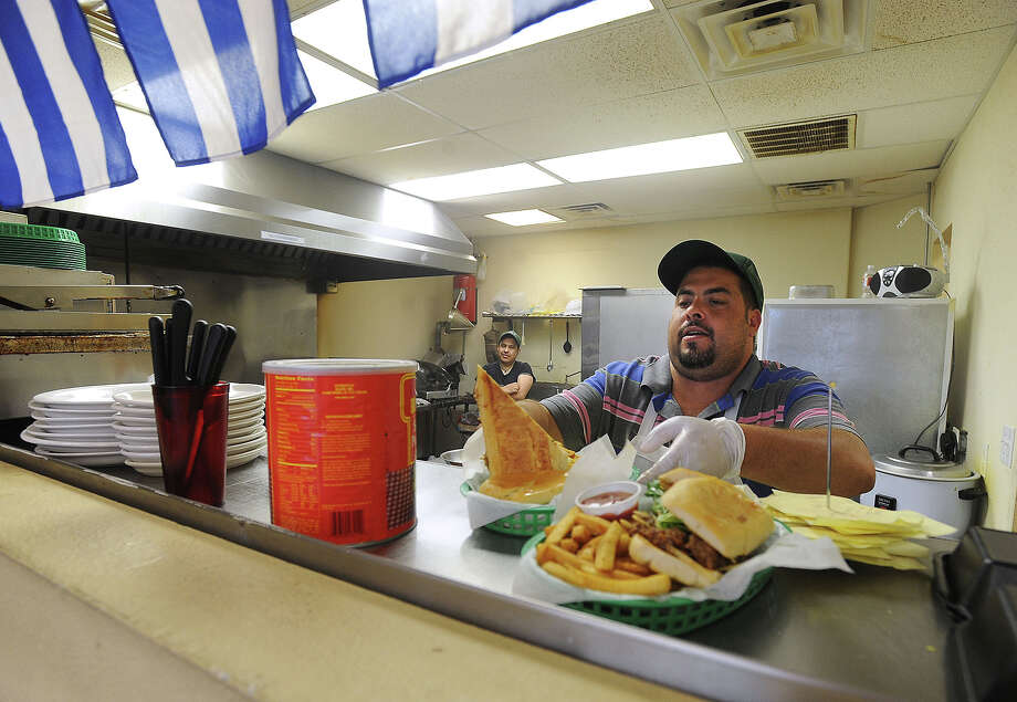 Chef and Owner Albert Miguez dishes up sandwiches at the service window at Tico's Cuban Cafe in Bridge City. Guiseppe Barranco/The Enterprise Photo: Guiseppe Barranco