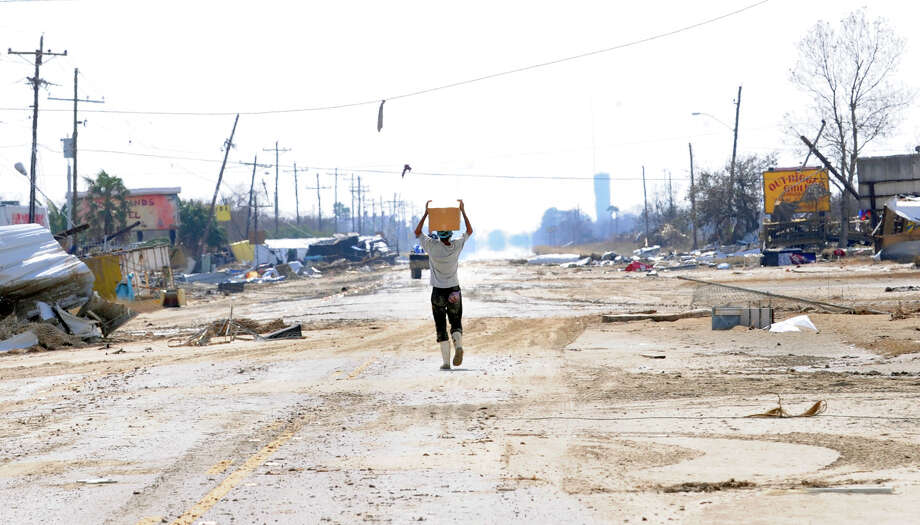 One of the last remaining residents of Crystal Beach carries a case of MRE rations down the middle of Highway 87 in what remains of Crystal Beach on Wednesday, September 17, 2008. Photo By: Valentino Mauricio Michael Clow rode out Hurricane Ike on Crystal Beach and has no plans to leave the area.