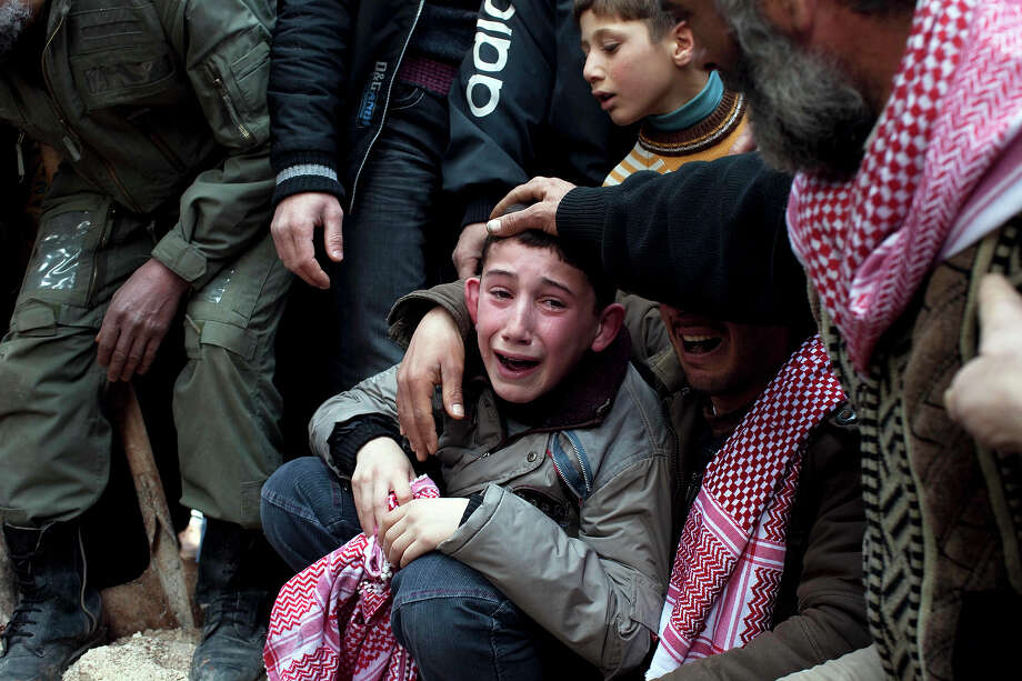 Ahmed, center, mourns his father Abdulaziz Abu Ahmed Khrer, who was killed by a Syrian Army sniper, during his funeral in Idlib, north Syria, Thursday, March 8, 2012. Photo: Rodrigo Abd, ASSOCIATED PRESS / AP2012