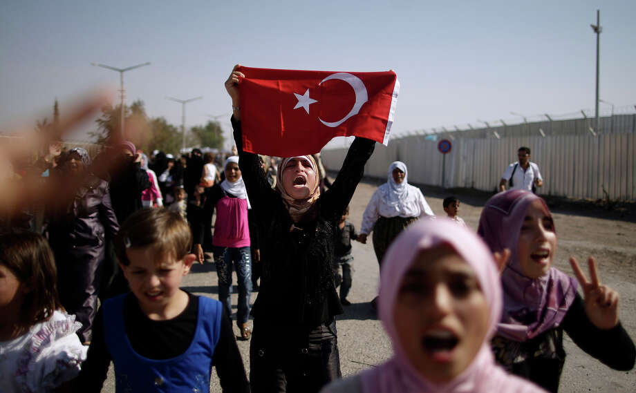 Syrians, who fled their homes due to fighting between the Syrian army and the rebels, shout slogans as they march toward the Turkish side of the border, during a protest asking the Turkish government to let them enter to their refugee camps, at the Bab Al-Salameh border crossing, near the Syrian town of Azaz, Tuesday, Aug. 28, 2012 Photo: Muhammed Muheisen, AP / 2012 AP