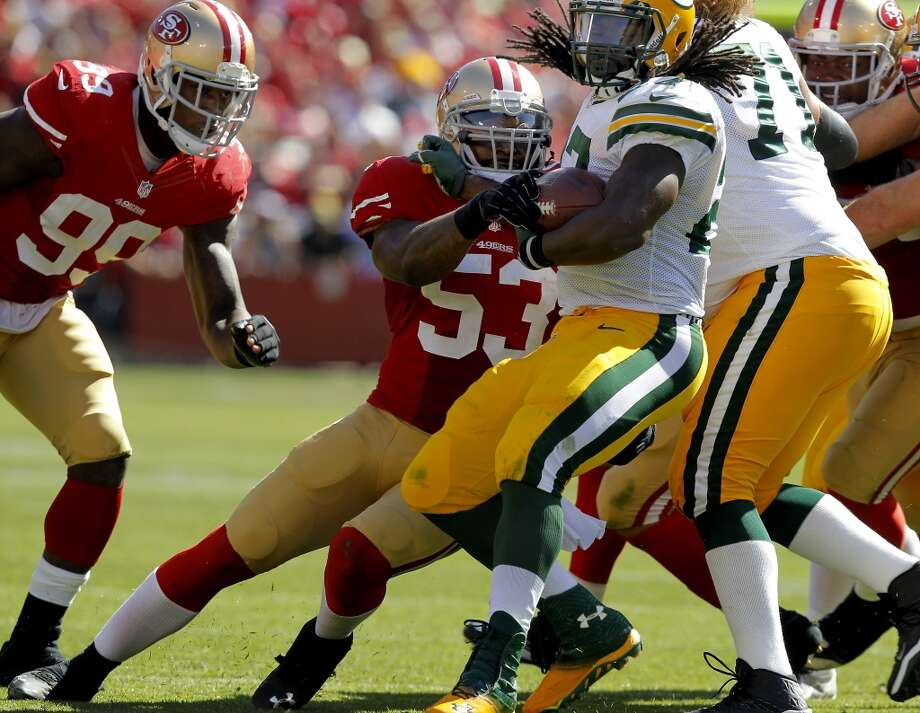 Green Bay's Eddie Lacey (27) is sandwiches between 49er defenders Sunday September 8, 2013. The San Francisco 49ers open their 2013 season with a 34-28 victory against the Green Bay Packers at Candlestick Park in San Francisco, Calif. Photo: Brant Ward, The Chronicle