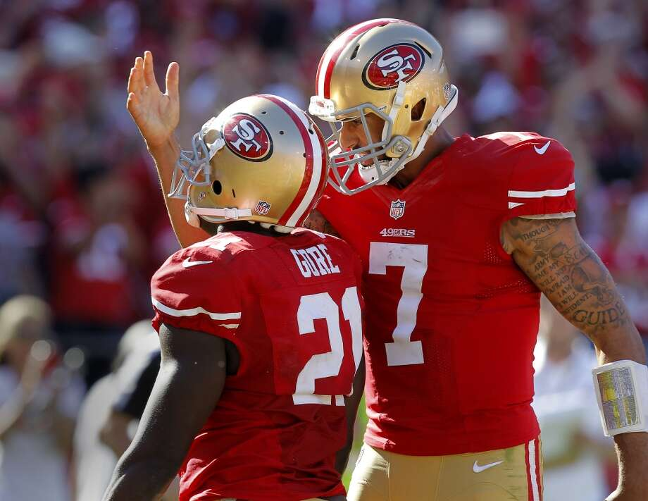 Colin Kaepernick (7) celebrated with Frank Gore (21) after Gore's touchdown in the second half Sunday September 8, 2013. The San Francisco 49ers open their 2013 season with a 34-28 victory against the Green Bay Packers at Candlestick Park in San Francisco, Calif. Photo: Brant Ward, The Chronicle