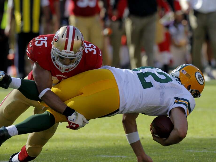 Aaron Rodgers is brought down by Eric Reid on a keeper in the second half Sunday September 8, 2013. The San Francisco 49ers open their 2013 season with a 34-28 victory against the Green Bay Packers at Candlestick Park in San Francisco, Calif. Photo: Brant Ward, The Chronicle