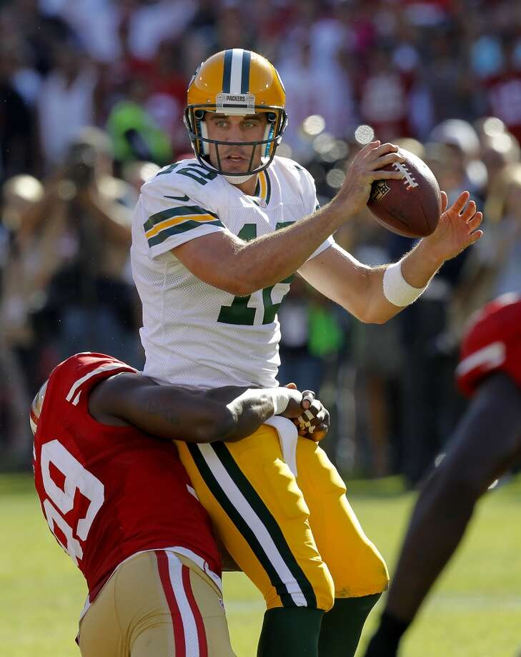 Aldon Smith (99) wraps up Aaron Rodgers on the last play of the game Sunday September 8, 2013. The San Francisco 49ers open their 2013 season with a 34-28 victory against the Green Bay Packers at Candlestick Park in San Francisco, Calif. Photo: Brant Ward, The Chronicle