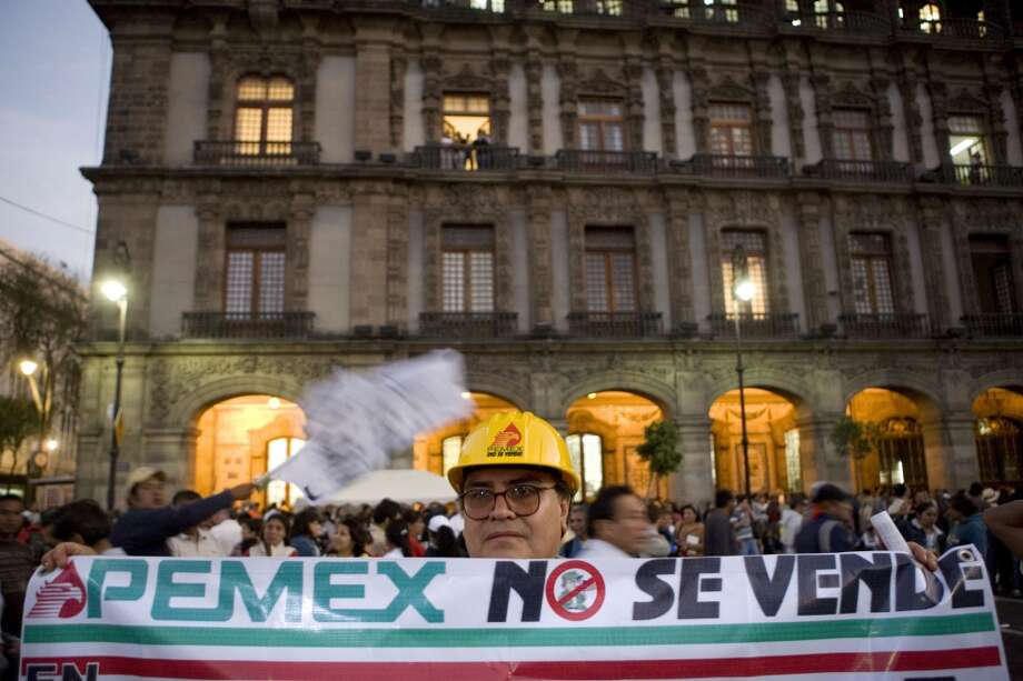 "A man holds a banner that reads in Spanish, ""Pemex is not for sale,"" at a political rally for presidential candidate Andres Manuel Lopez Obrador in the Zocalo in Mexico City. President Enrique Pena Nieto's proposal to revamp energy policy and modernize Pemex, expected to be unveiled in August 2013, is igniting an enormous political fight, not just for the oil industry but for the entire country. (AP Photo/Alexandre Meneghini, File) Photo: Alexandre Meneghini, Associated Press"