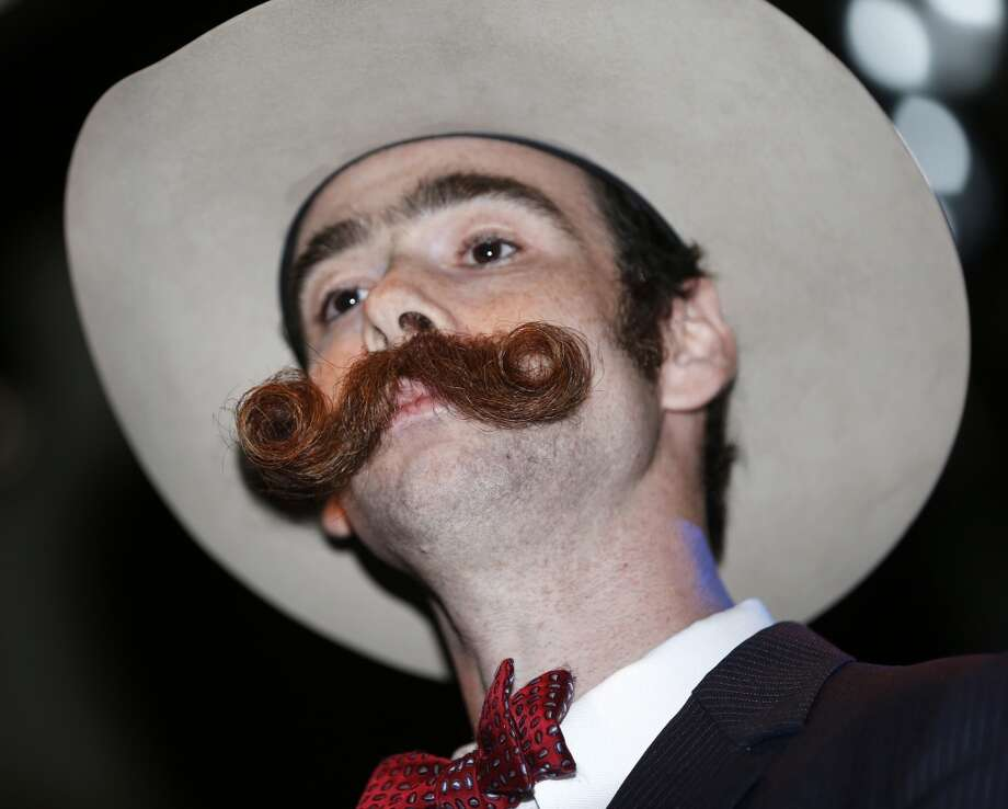 Devon Holcombe of Jacksonville, Fla., poses for the crowd before continuing on to win a gold medal in the Natural Moustache division during the fourth annual Just For Men National Beard and Moustache Championships. Photo: Susan Poag, Associated Press