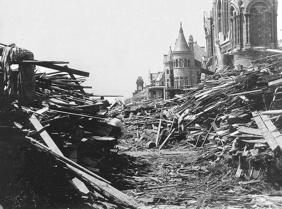 Sept. 8, 1900: The Gresham house,  center, now known as the Bishop's Palace, sits relatively unscathed behind a wall of debris following the hurricane that devastated Galveston, Texas. More than 6,000 people were killed and 10,000 left homeless as entire neighborhoods were swept clean. Sacred Heart Catholic Church, at right, was heavily damaged. Photo: AP / SISTERS OF CHARITY