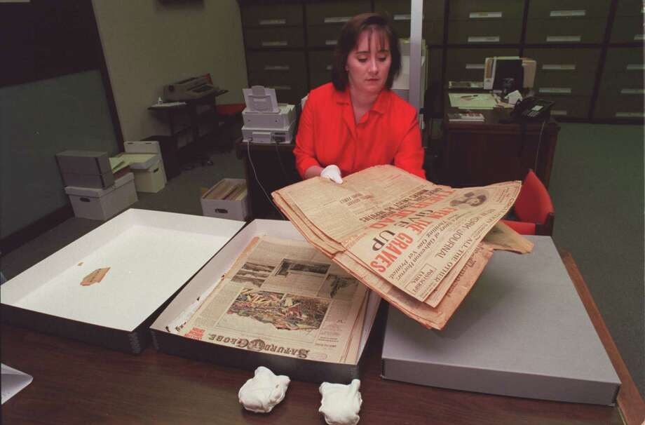 July 18, 2000: Shelly Henley Kelly works with old newspapers covering the 1900 storm at the Rosenberg Library in Galveston, Texas Photo: E. Joseph Deering, Houston Chronicle / Houston Chronicle