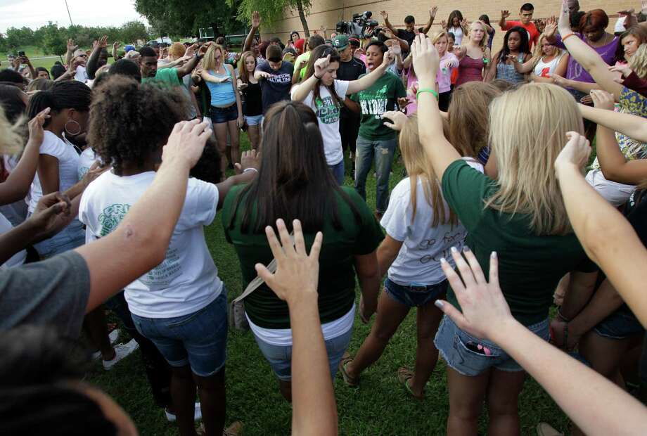 More than 200 people pray together outside Spring High School Sunday, Sept. 8, 2013, in Spring. Students will return to classes on Monday to the school where Joshua Broussard, 17, a Spring High School student was fatally stabbed and three others injured at the school Wednesday, Sept. 3, 2013.  Luis Alonzo Alfaro, 17, has been charged with murder. Photo: Melissa Phillip, Houston Chronicle / © 2013  Houston Chronicle