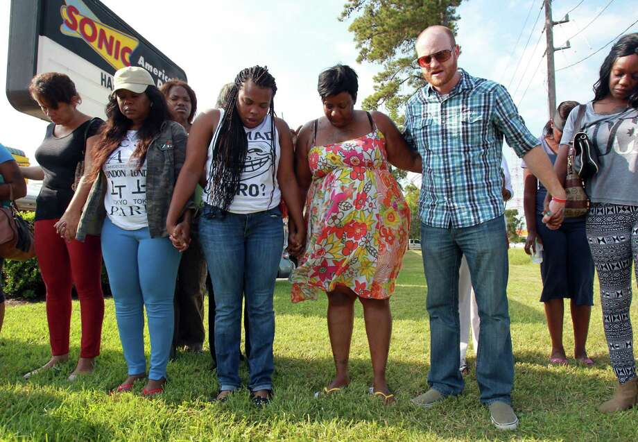 Parents, family and friends hold hands in prayer for the  victims of the fatal stabbing at Spring High School on Wednesday, Sept. 4, 2013, in Spring. Photo: Mayra Beltran, Houston Chronicle / © 2013 Houston Chronicle