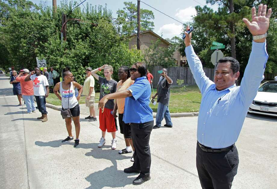 Eric Estrada tries to wave at his daughter, who is a junior, from across the street from Spring High School where a student was fatally stabbed and three others injured Wednesday, Sept. 4, 2013, in Spring. Many students could be seen by their parent from across the street, but they were contained outside in the bus area for some time before their were allowed to leave. Photo: Melissa Phillip, Houston Chronicle / © 2013  Houston Chronicle